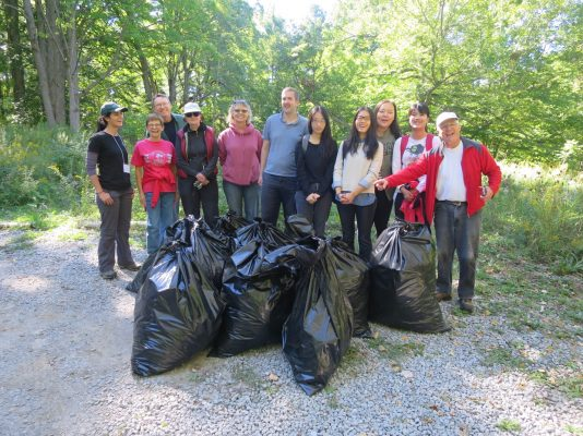 A group of 11 people with many filled garbage bags in front