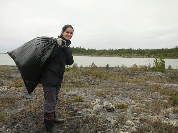 A girl beside a river holding a full garbage bag