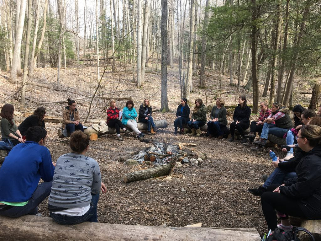 About 20 people sitting around a daytime campfire