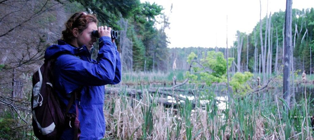 Hiker with binoculars looking at a wetland