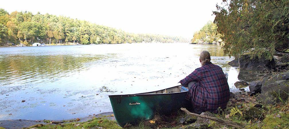 Stephen MacFarlane sitting on shoreline with a canoe