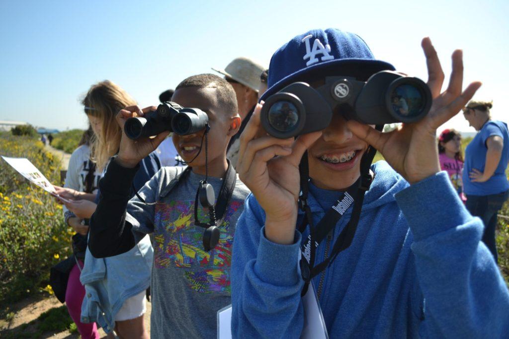 Kids wtih binoculars learning outside