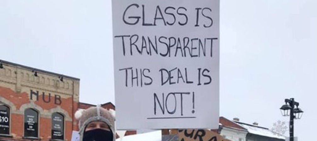 """Glass is Transparent_This Deal Is Not"" sign at rally"