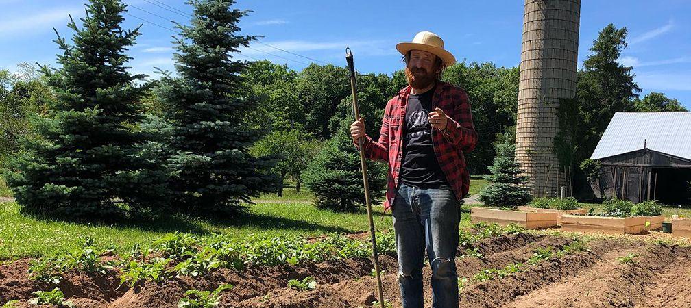 Spencer tilling rows on the farm